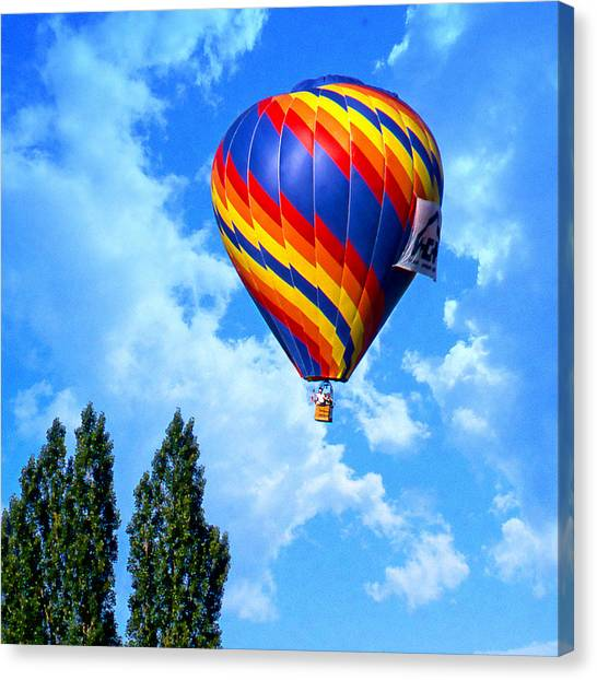 Clearing The Tree Tops Canvas Print by Ken Evans