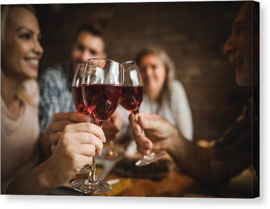 Close Up Of A Family Toasting With Red Wine At Home. Canvas Print by Skynesher