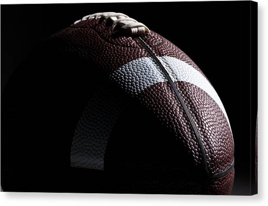 Close-up Of American Football With Dramatic Lighting Canvas Print by Kledge