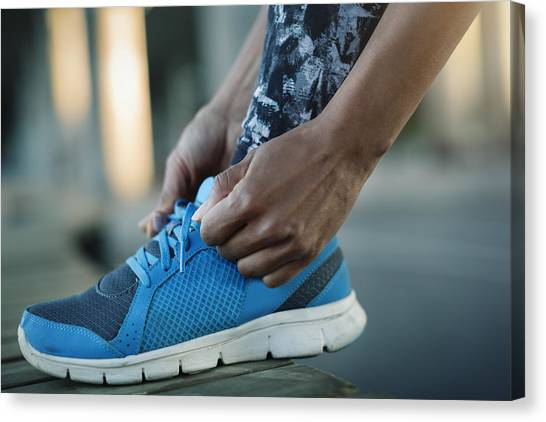 Close-up Of Woman Tying Shoelace On Bench Canvas Print by Maskot