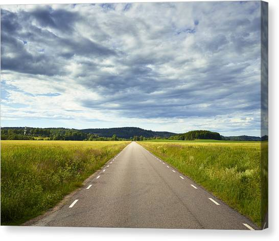 Clouds Above Country Road Canvas Print by Johner Images