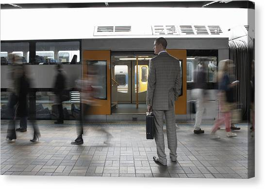 Commuters Passing Businessman On Platform,  (blurred Motion) Canvas Print by Toby Burrows