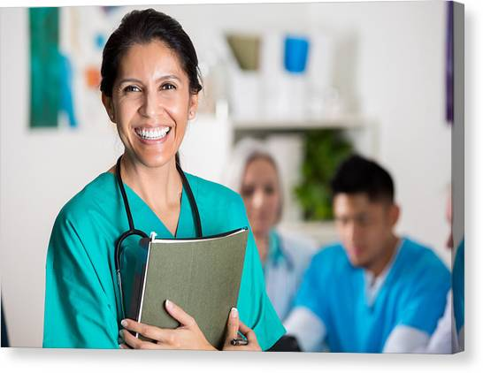 Confident Doctor In Medical Staff Meeting Canvas Print by Steve Debenport