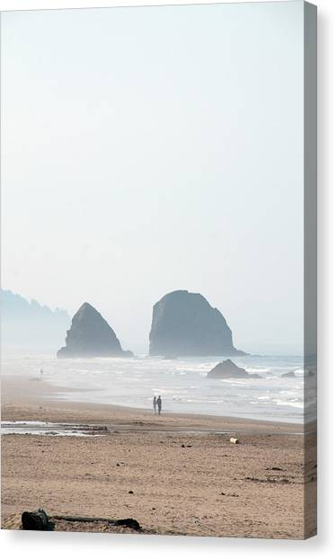 Couple Walking On Rocky Beach Canvas Print