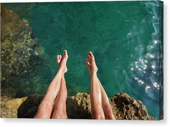 Couples Legs Above Turquoise Ocean Canvas Print by Picturegarden