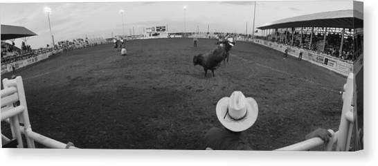 Bull Riding Canvas Print - Cowboy Riding Bull At Rodeo Arena by Panoramic Images