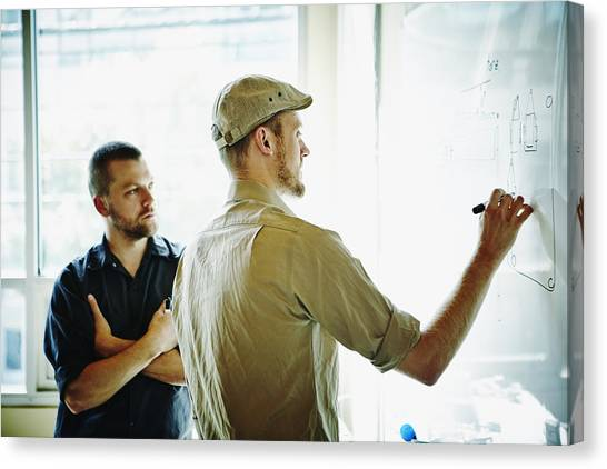 Coworkers Working On Project On Whiteboard Canvas Print by Thomas Barwick