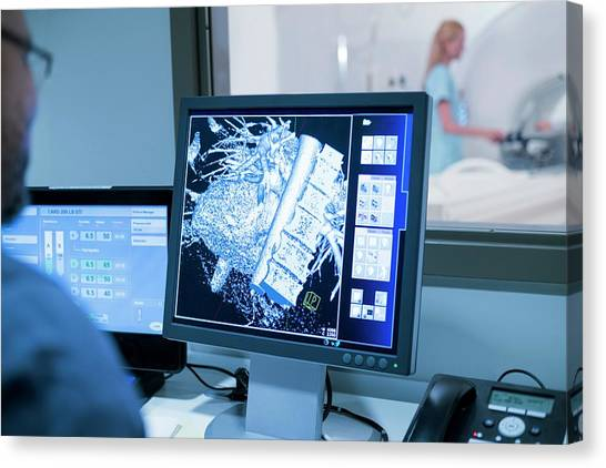 Doctor Looking At Mri Scans On Monitor Canvas Print by Science Photo Library