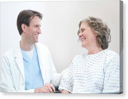 Doctor Smiling At Woman Patient Canvas Print by Science Photo Library