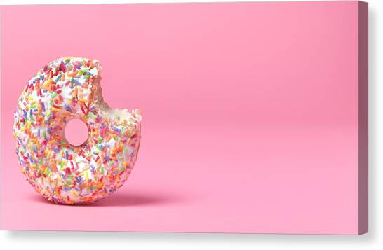 Doughnut On Pink With Bite Out Canvas Print by Peter Dazeley