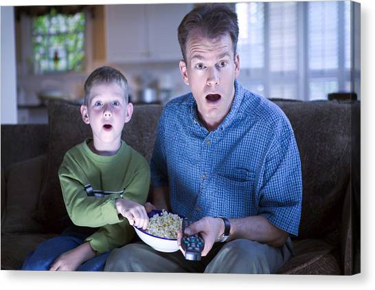 Father And Son With Remote Control And Popcorn Canvas Print by Thinkstock Images
