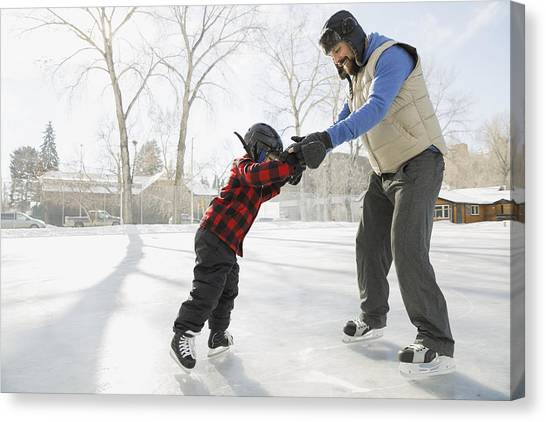 Father Teaching Son To Ice-skate On Outdoor Rink Canvas Print by Hero Images
