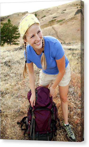 Backpacks Canvas Print - Female Smiing While Packing Her Bag by Jordan Siemens