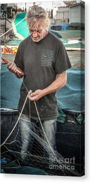 fisherman mending nets on Anzio harbour Canvas Print