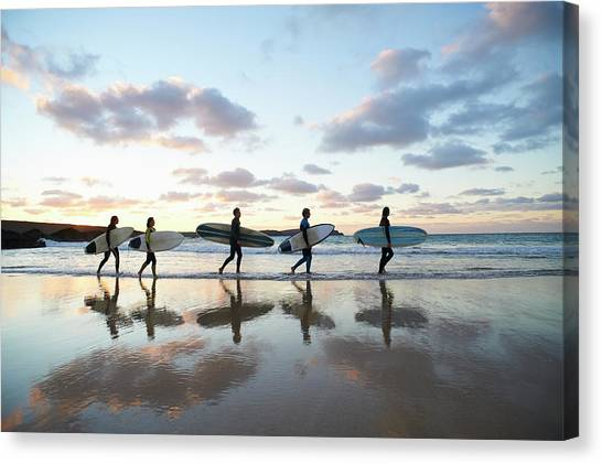 Five Surfers Walk Along Beach With Surf Canvas Print