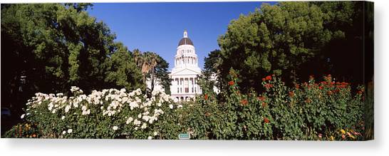 Big West Canvas Print - Flowers And Trees In Garden by Panoramic Images