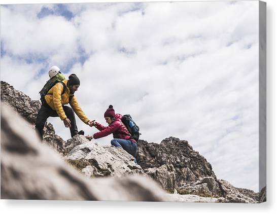 Germany, Bavaria, Oberstdorf, Man Helping Woman Climbing Up Rock Canvas Print by Westend61