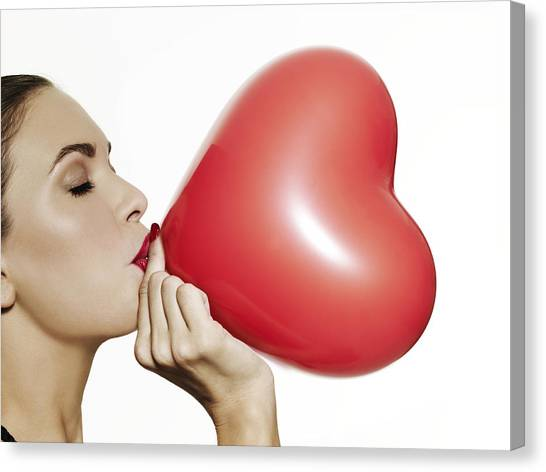 Girl Blowing Up A Red Heart Shaped Balloon Canvas Print by Elizabeth Hachem