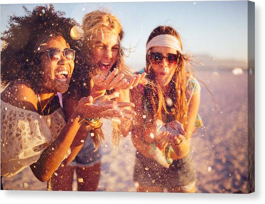 Girls Blowing Confetti From Their Hands On A Beach Canvas Print by Wundervisuals