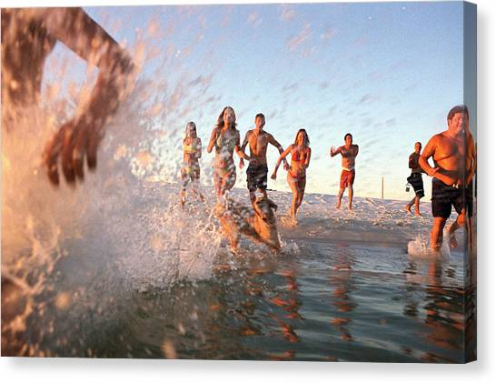 Group Of Young Adults Running Through Water At Ocean's Shore Canvas Print by Sean Murphy