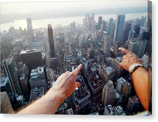 Hands Pointing At City As Seen From Canvas Print by Chris Tobin
