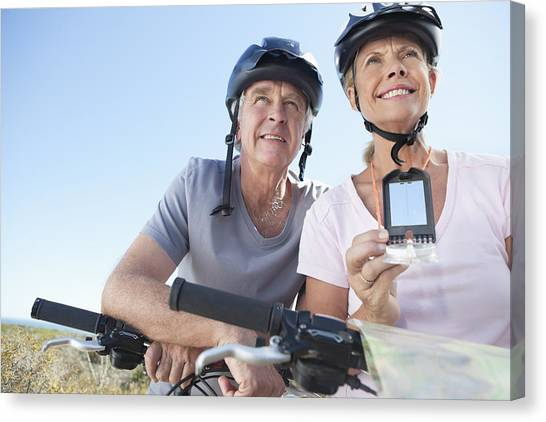 Happy Mature Woman Mountain Biking With Man Using Gps Canvas Print by OJO Images