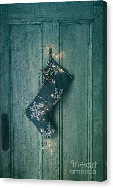 Holiday Stocking With Lights Hanging On Old Door Canvas Print