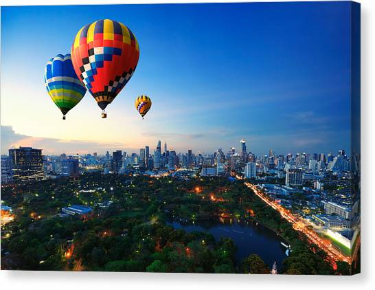 Hot Air Balloons Fly Over Cityscape At Sunset Background Canvas Print by Busakorn Pongparnit