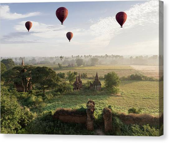 Hot Air Balloons Flying Over Ancient Canvas Print by Martin Puddy