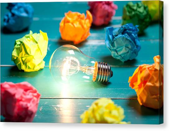 Incandescent Bulb And Colorful Notes On Turquoise Wooden Table Canvas Print by Xxmmxx
