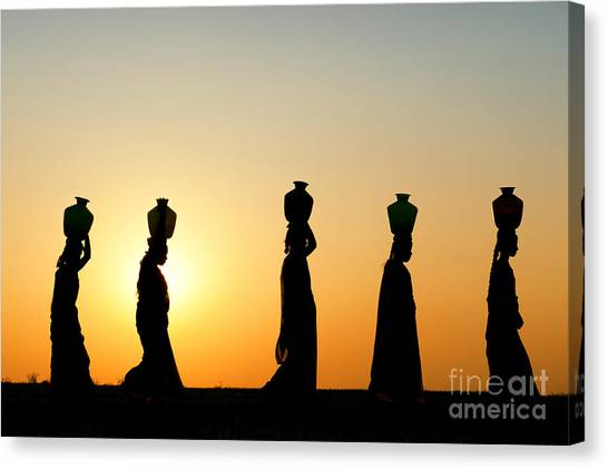 Indian Canvas Print - Indian Women Carrying Water Pots At Sunset by Tim Gainey