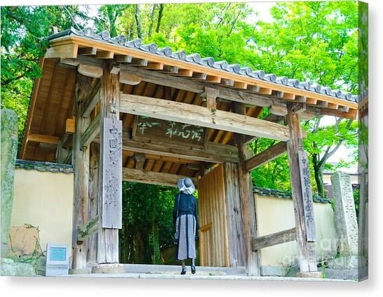 Lady Looking Up At The Impressive Woodwork Of A Japanese Temple Gate Canvas Print