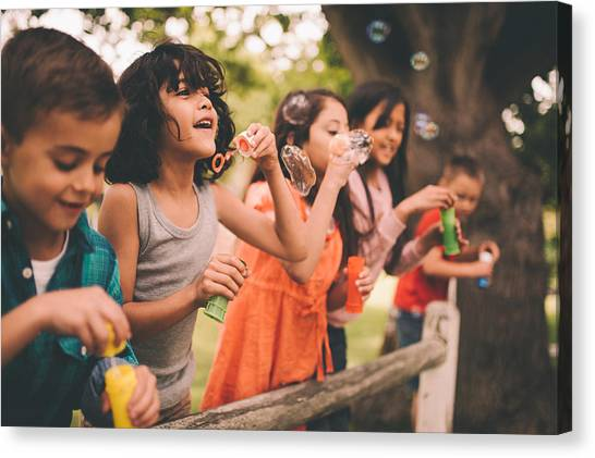 Little Boy Having Fun With Friends In Park Blowing Bubbles Canvas Print by Wundervisuals