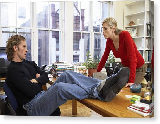 Male Office Worker With Feet On Desk, Woman Leaning On Edge Of Desk Canvas Print by Christopher Robbins
