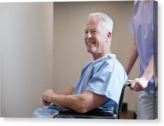 Man In Hospital Gown In Wheelchair Canvas Print by Science Photo Library