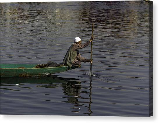Man Plying A Wooden Boat On The Dal Lake Canvas Print