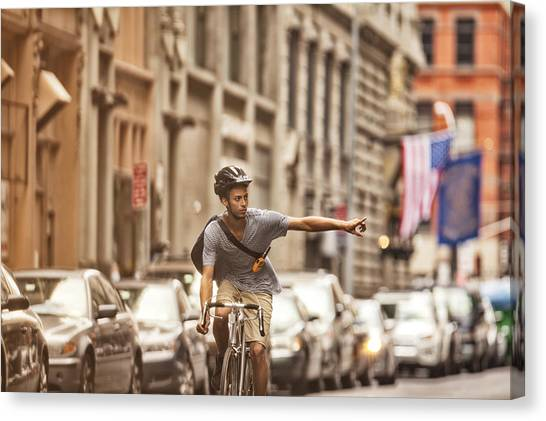 Man Riding Bicycle On City Street Canvas Print by Sam Edwards
