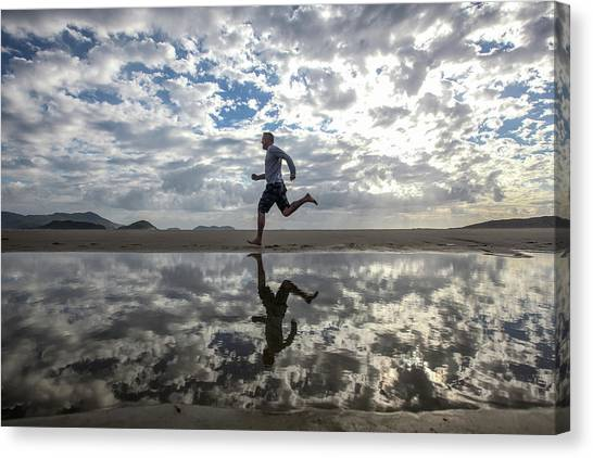 Man Running On Beach Canvas Print by Paul Mansfield Photography