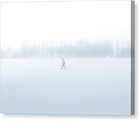 Man Walking Through A Snowfield Canvas Print by Taketan