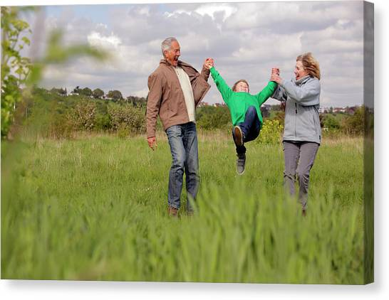 Mature Couple Swinging Grandchild In Canvas Print by Bloom Productions