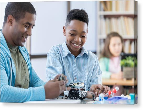 Mentor And Male Student Working Together On A Robot Canvas Print by Steve Debenport