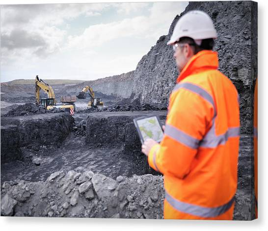 Protective Clothing Canvas Print - Miner Checks Plans On Digital Tablet In by Monty Rakusen