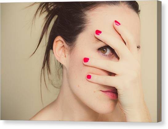 Misterious Girl With Red Nails And Hand On Face. Canvas Print by Volanthevist