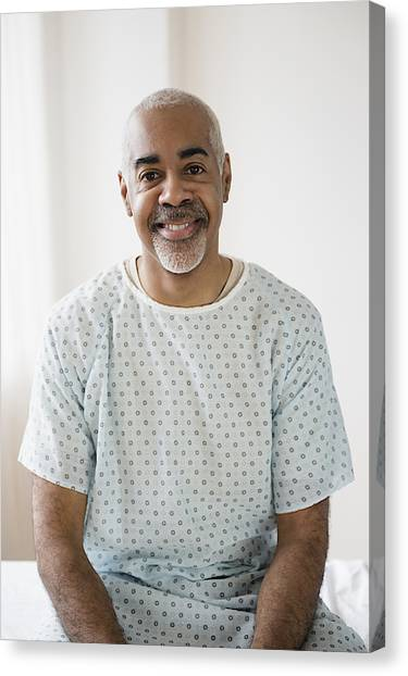 Mixed Race Older Man Sitting On Hospital Bed Canvas Print by JGI/Jamie Grill