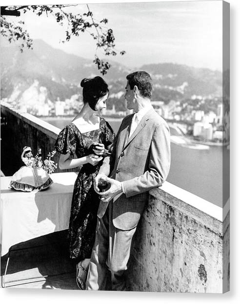 Models Holding Wine On A Balcony Canvas Print