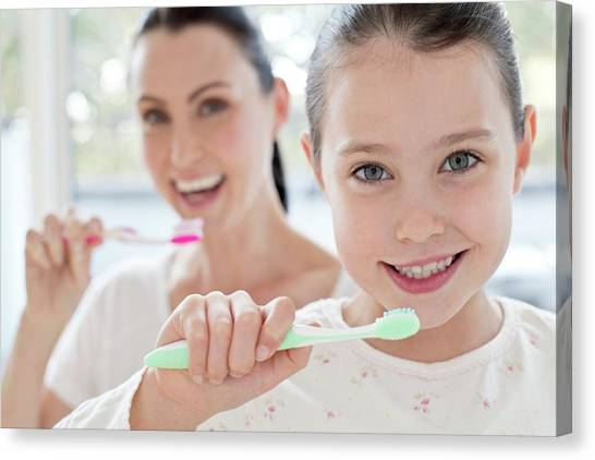 Toothbrush Canvas Print - Mother And Daughter Brushing Teeth by Science Photo Library