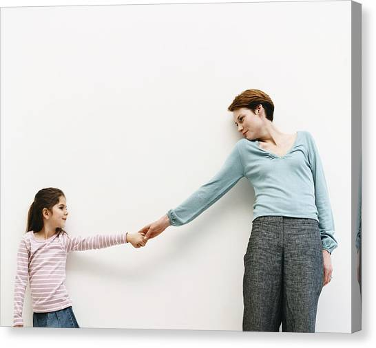 Mother And Her Daughter Stand By A Wall, Reaching Out And Holding Hands Canvas Print by Dylan Ellis