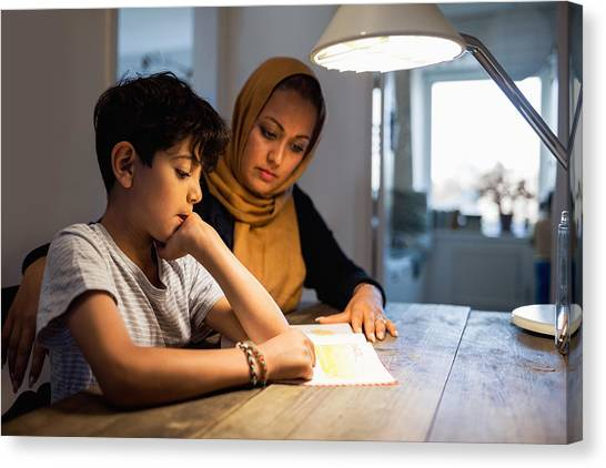 Mother And Son Reading Book Under Illuminated Desk Lamp At Home Canvas Print by Maskot