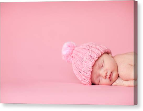 Newborn Baby Girl Sleeping Peacefully On Pink Background Canvas Print by Ideabug