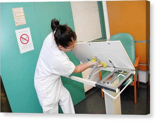 Nurse Cleaning Hospital Table Canvas Print by Aj Photo/science Photo Library